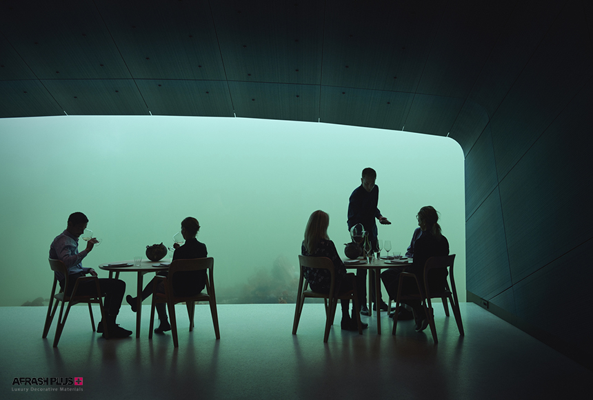 رستوران زیرآبی به همراه میهمان و گارسون در حال سرو شراب