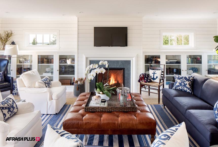 نشیمن وینتیج با دیواره چوبی سفید و جلو مبلی چرم قهوه ای و مبلمان سفید و آبی و شومینه سنگی