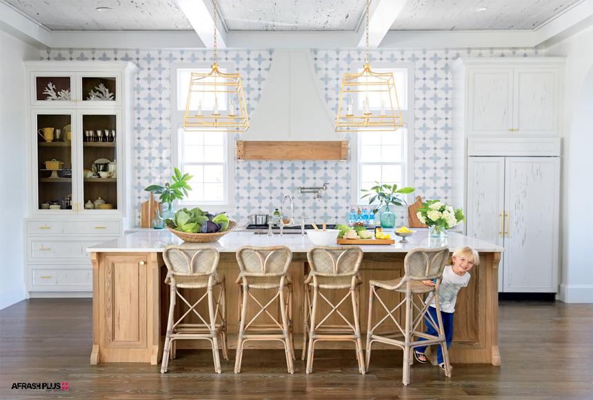 آشپزخانه سبک ساحلی با دیوا کاشی و کابینت چوب سفید و پسر بچه خندان در مقابل جزیره