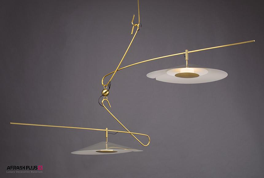 لامپ آویز طلایی رنگ با طراحی پست مدرن در زمینه طوسی