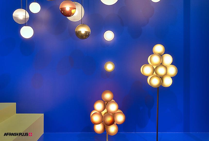 لامپ خوشه ای آویز و ایستاده در زمینه دیوار آبی