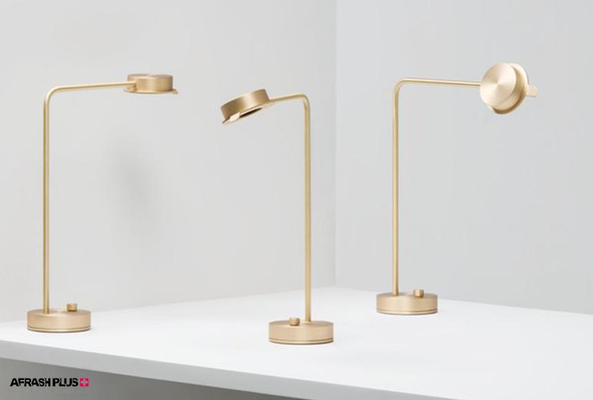 میز سفید رنگ به همراه لامپ رومیزی طلایی