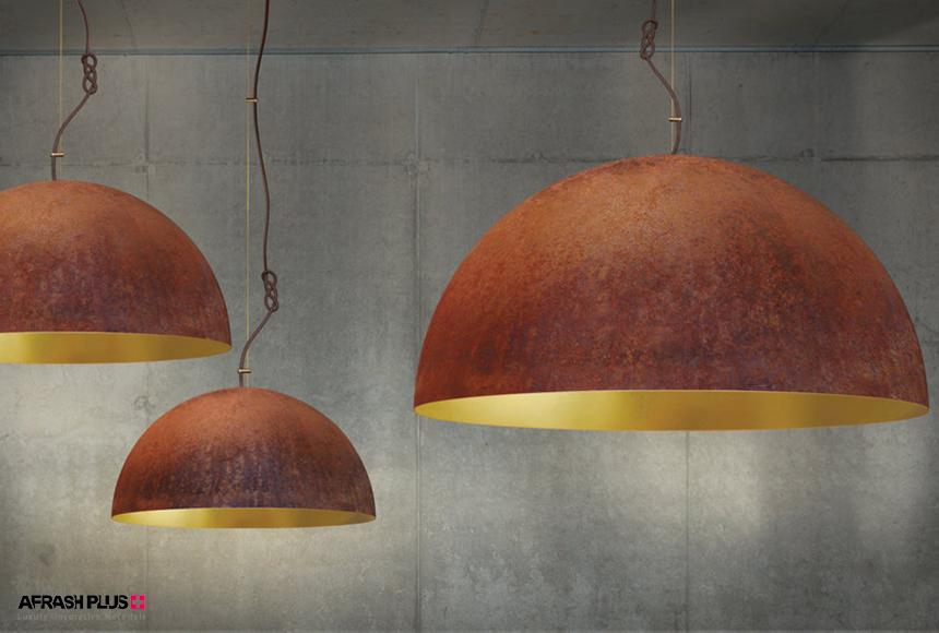 لامپ آویز استیل زنگ زده و توکاری طلا در زمینه دیوار بتنی