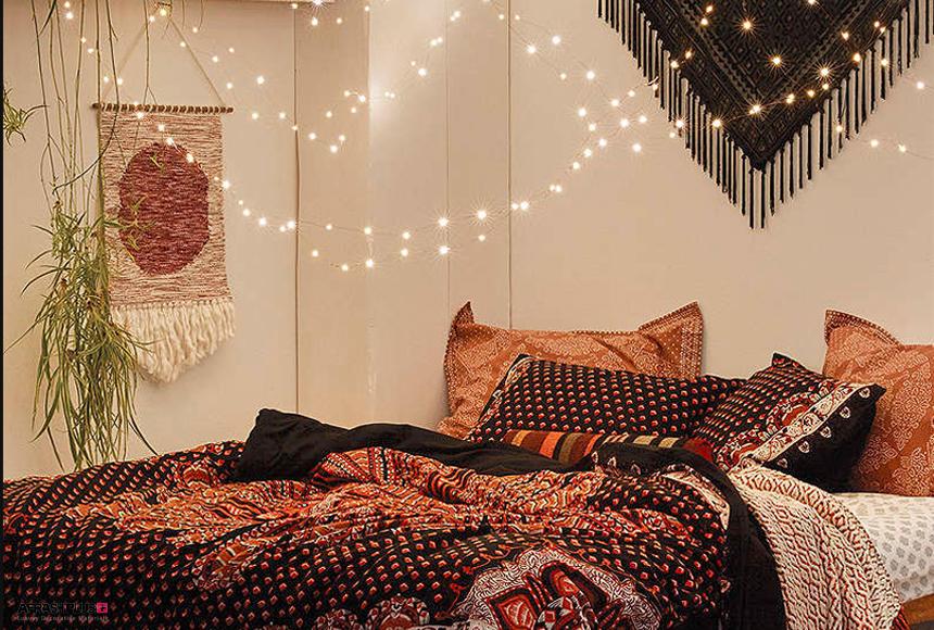 اتاق خواب سبک کولی با دیوار سفید و روتختی تیره طرح دار