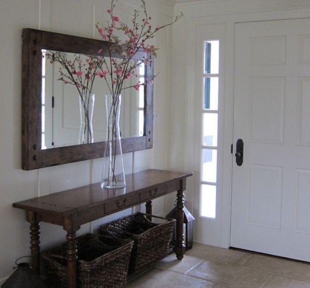 کارایی آیینه در دکوراسیون: استفاده از آینه و کنسول چوب در کنار درب ورودی