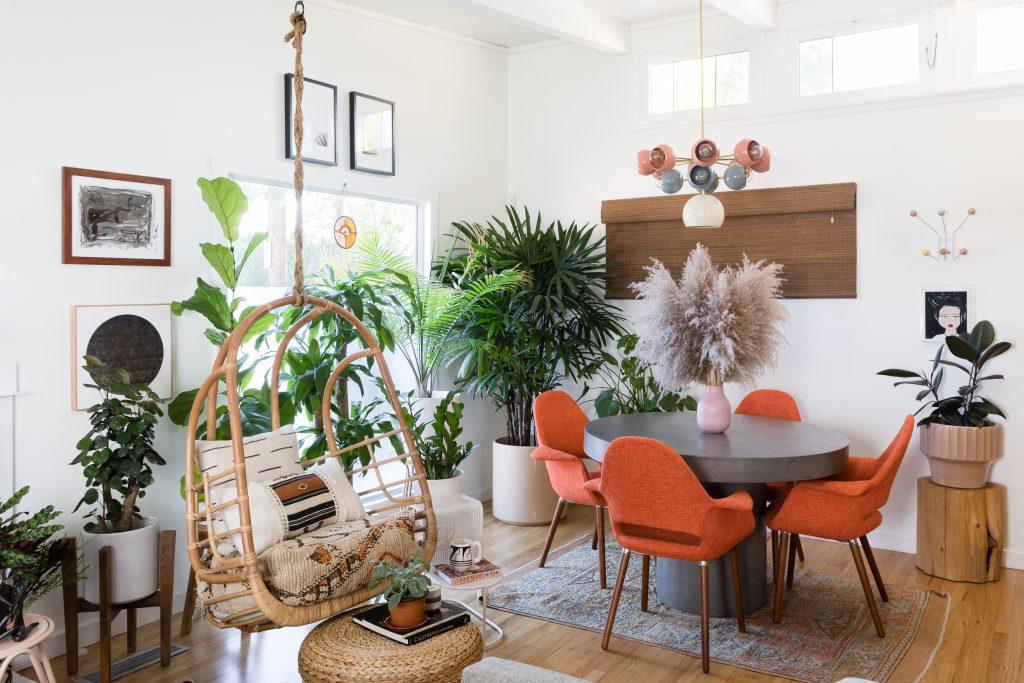نشیمنی سرسبز که در آن یک میز طوسی با صندلی های نارنجی و یک تاب در سمت چپ اتاق واقع شده است.