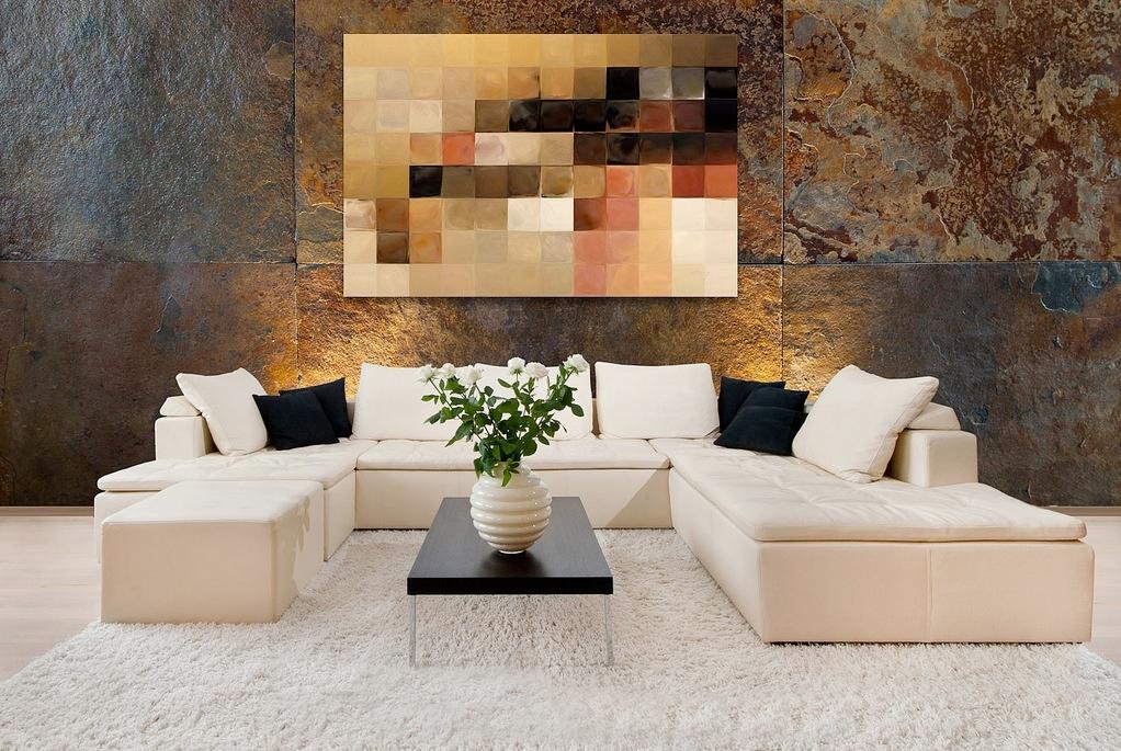 دکوراسیون منزل با مبل های کرم رنگ که دیواری با طرح سنگ دارد و تابلویی بر روی دیوار با رنگ های قهوه ای رنگ