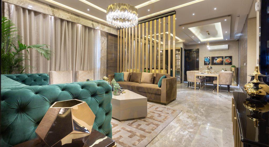فضای نشیمنی بزرگ با مبل های کرم و آبی فیرزوه ای و پرده ای کرم رنگ با دیوار جدا کننده که که  نوار های چوبی باریک دارد