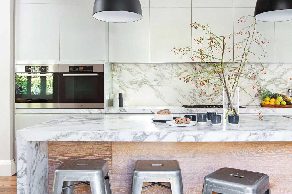 نمای آشپز خانه ای با سبک مدرن که کابینت های بدون دستیگره و فشاری دارد.