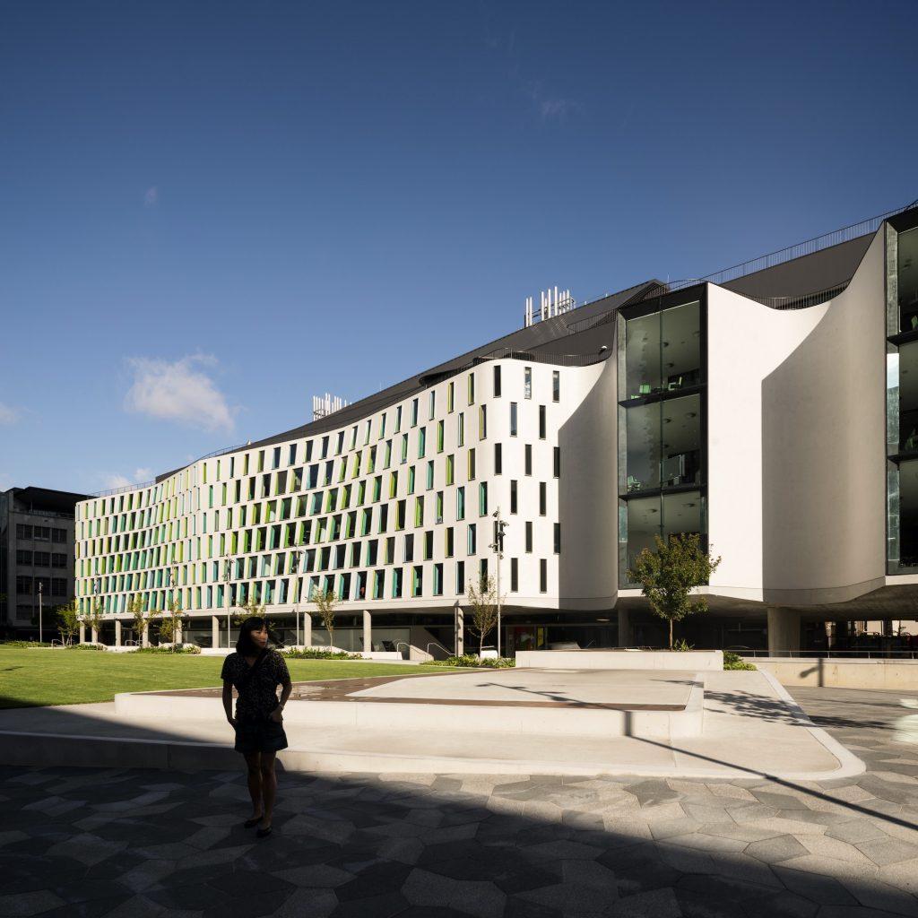 تصویر یک ساختمان بزرگ مدرن که با متریال سفید رنگ کار شده است و آسمان صاف آبی و آفتابی که مطابق با اقلیم ساخته شده است.