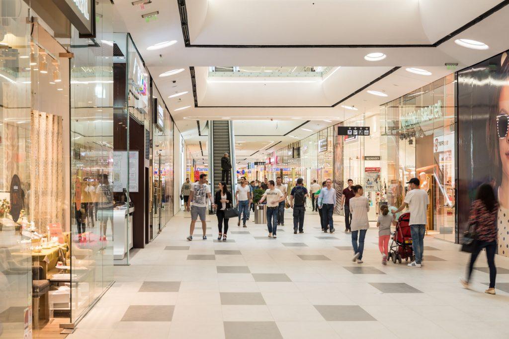 مرکز خرید مدرن با کف و سقف سفید و مغازه های شیشه ای که مراجعه کنندگان مشغول خرید می باشند.