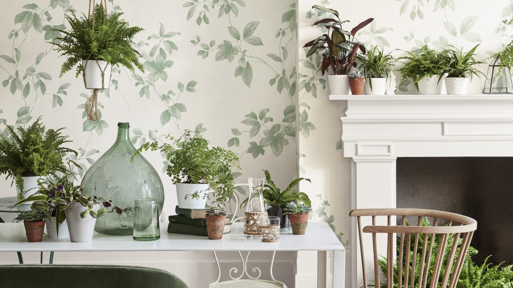 تصویری یک اتاق با کاغذ دیواری طرح برگ و یک میز سفید پر از گل و یک شومینه سفید رنگ که پر از گلدان های کوچک طبیعی می باشد.