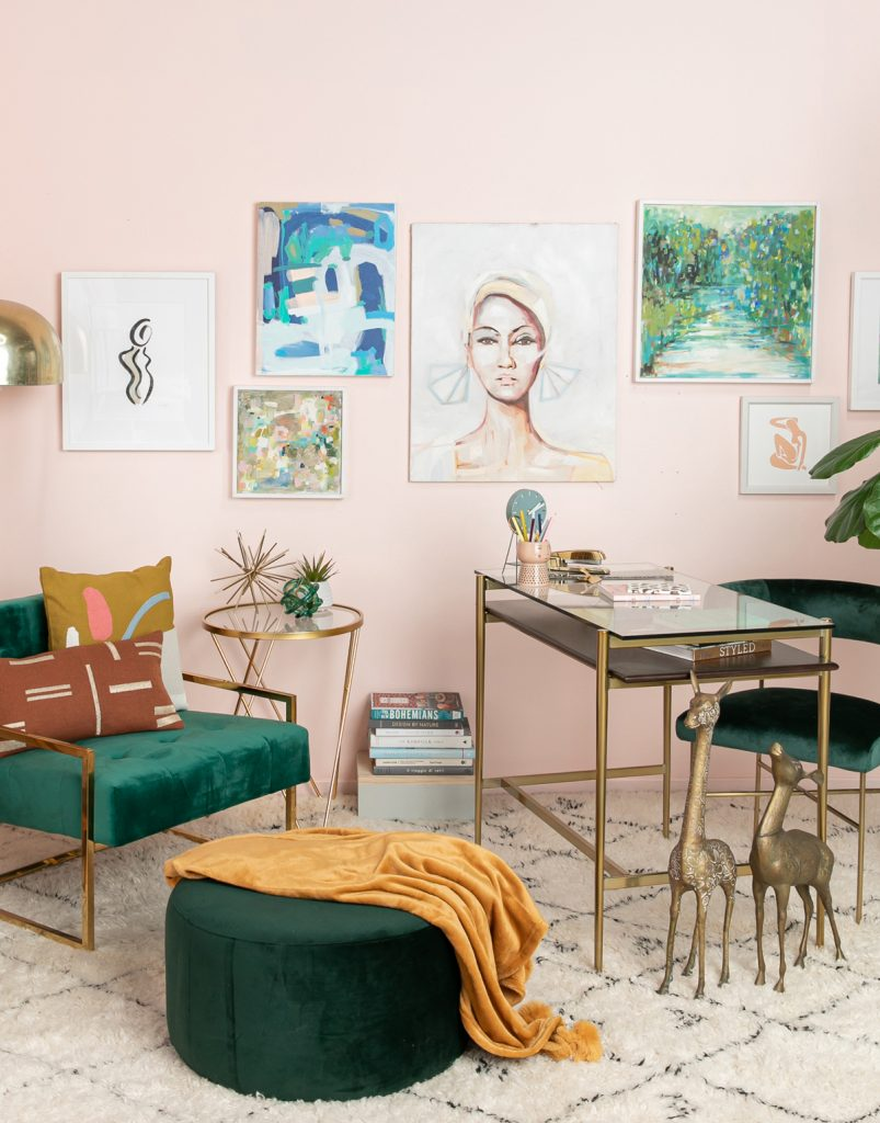 اتاقی با دیوار صورتی کمرنگ که میزی کوچک در گوشه اتاق هست و صندلی کوچکی سبز رنگ روبروی آن،دیواری پر شده از تابلو