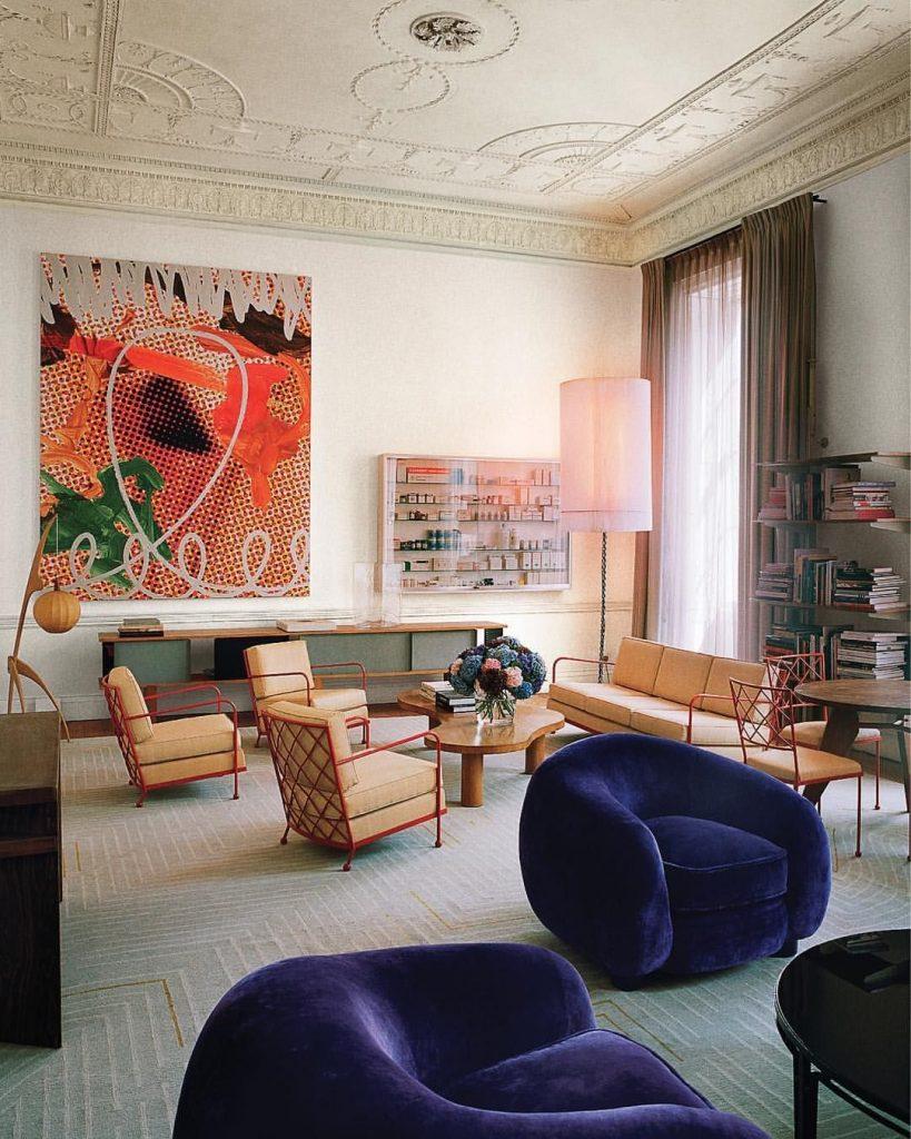 فضای نشیمن  بزرگ با دو ست مبل به رنگ کرم و سرمه ای با تابلویی نقاشی در مرکز دید