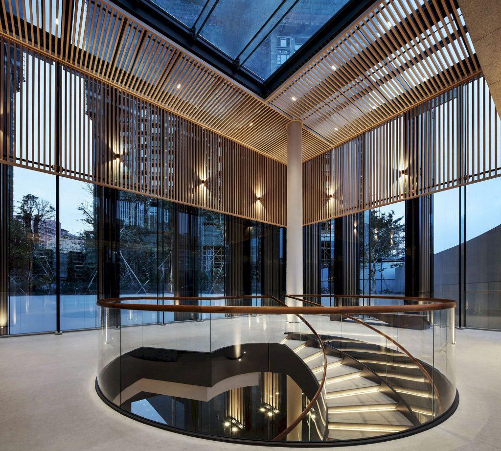 تصویر یه راه پله که در وسظ یک مرکز تجاری قراردارد و دیوارهای شیشه ای که با ابزار آلات به رنگ چوب تزیین شده است.