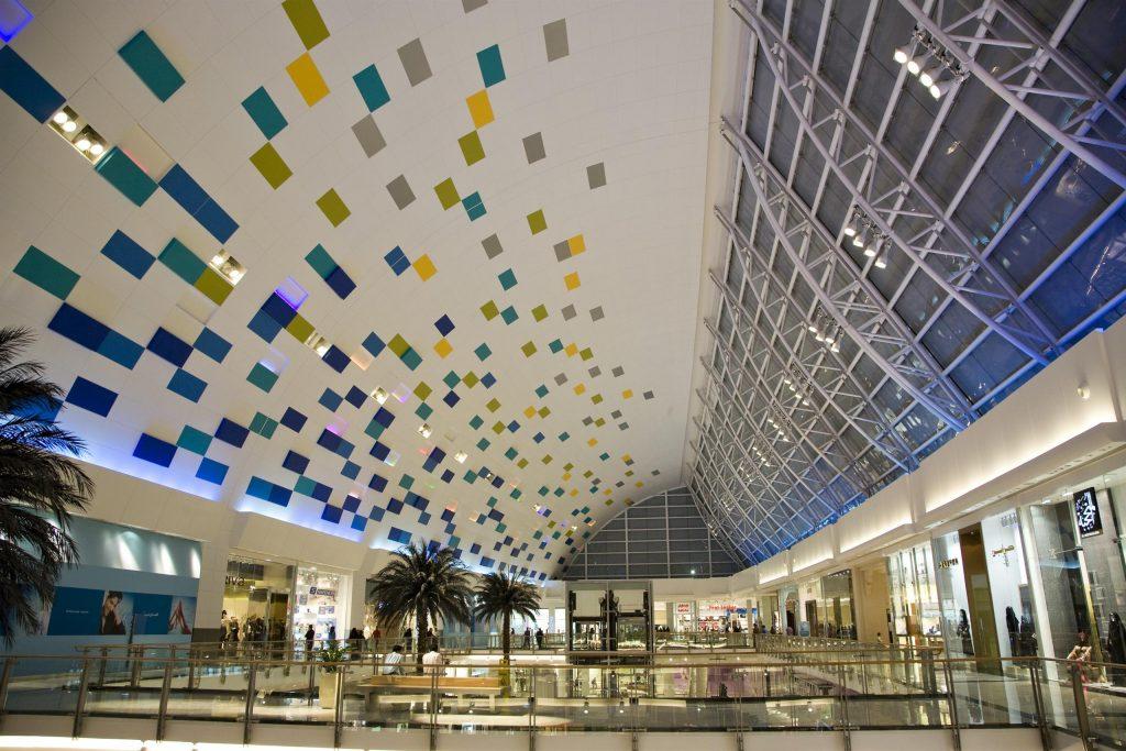 تصویر یک مرکز خرید با سقف بلند مثلثی شکل و متریال رنگی  آبی و سز و زرد و طوسی و شیشه.