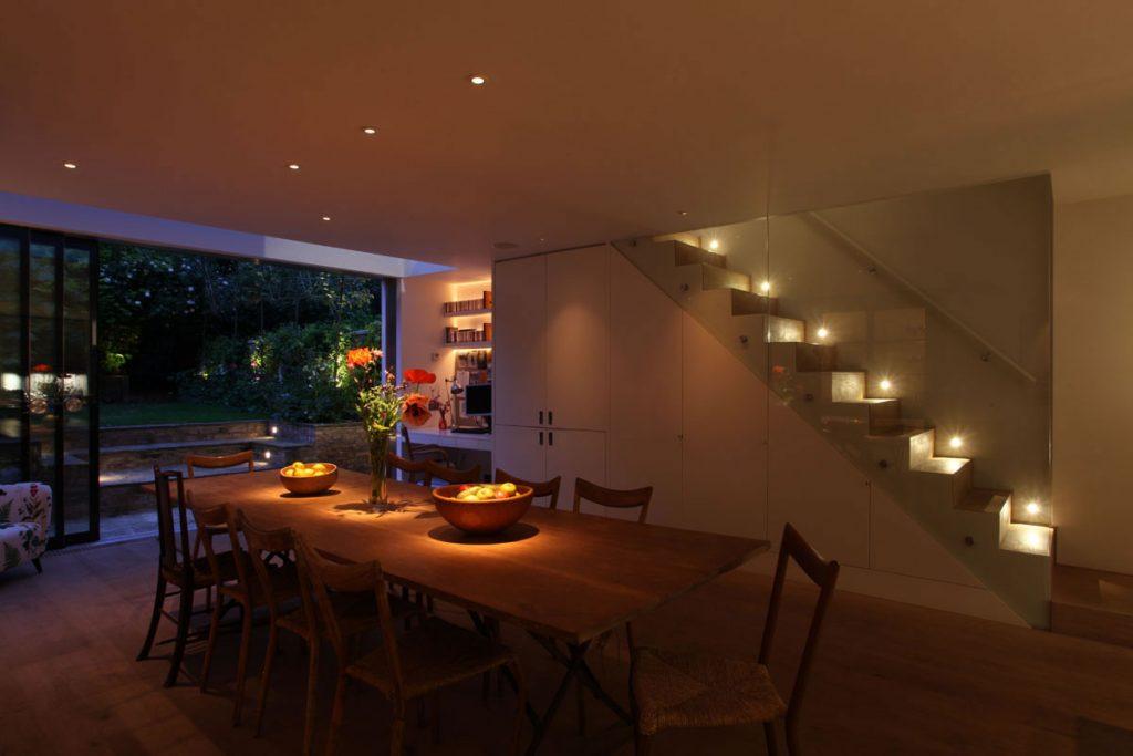 فضای پذیرایی با نورپردازی سقفی و چراغ های کار شده در راه پله