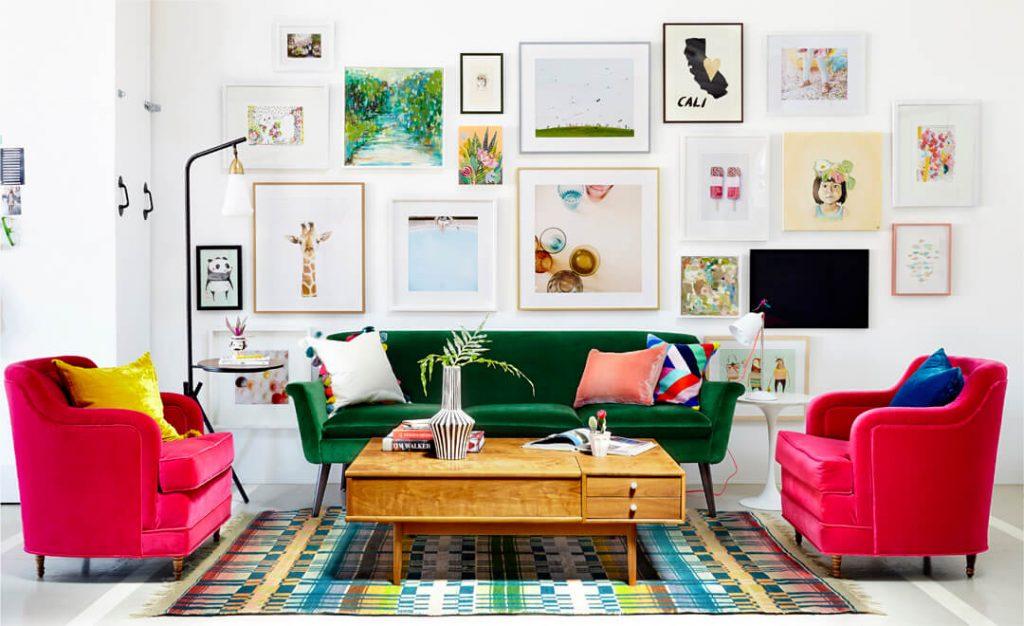 دکوراسیون منزل با کاناپه سبز رنگ و مبل های تک نفره سرخابی رنگ و میز جلوی آنها و دیواری پر شده از تابلو