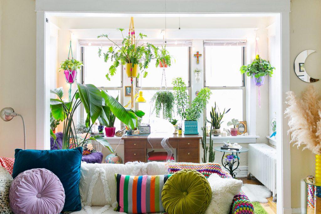 یک نشیمن با یک پنجره ی بزرگ که یک میز تحریر زیر پنجره قرار دارد و با وسایل و گل دان های رنگی تزیین شده است.