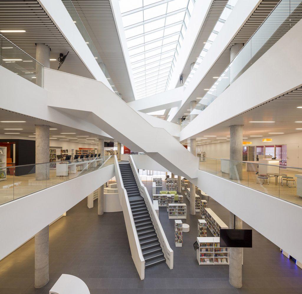 تصویر یک مرکز تجاری مدرن با متریال سفید رنگ و پله های ضربدری. طبقه اول و دوم کتابخانه می باشد.