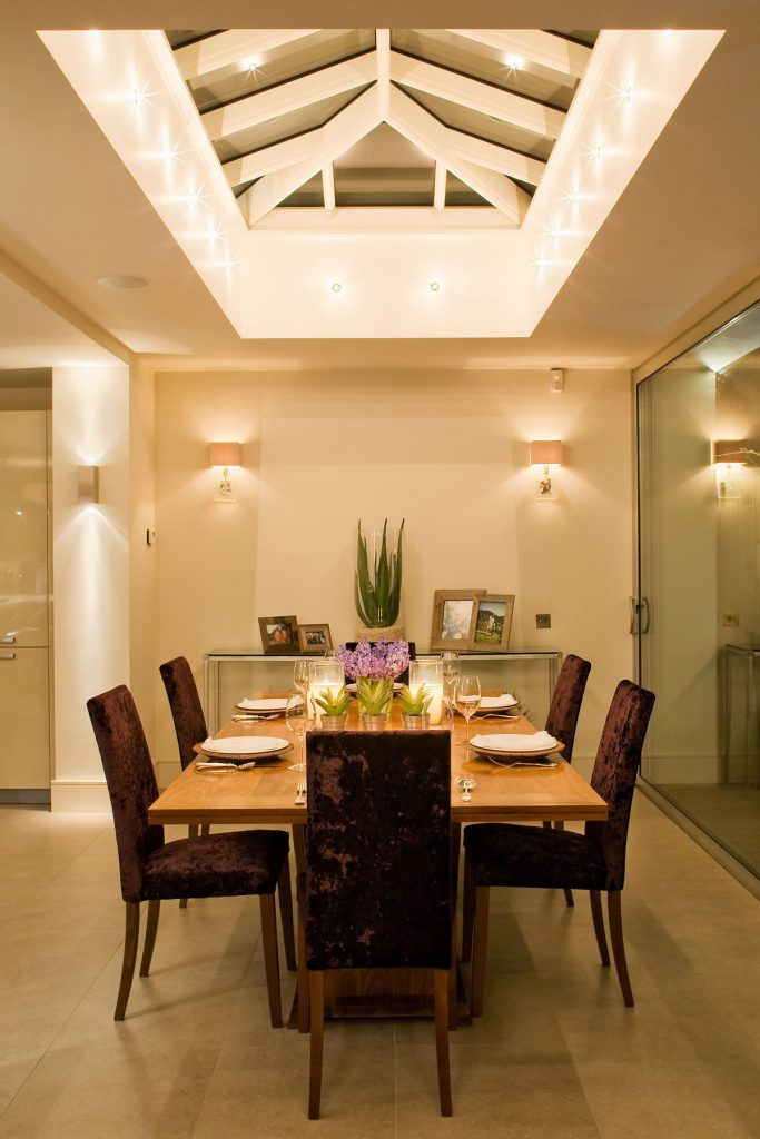 فضای ناهارخوری که با چراغ های سقفی و دیواری نور پردازی شده