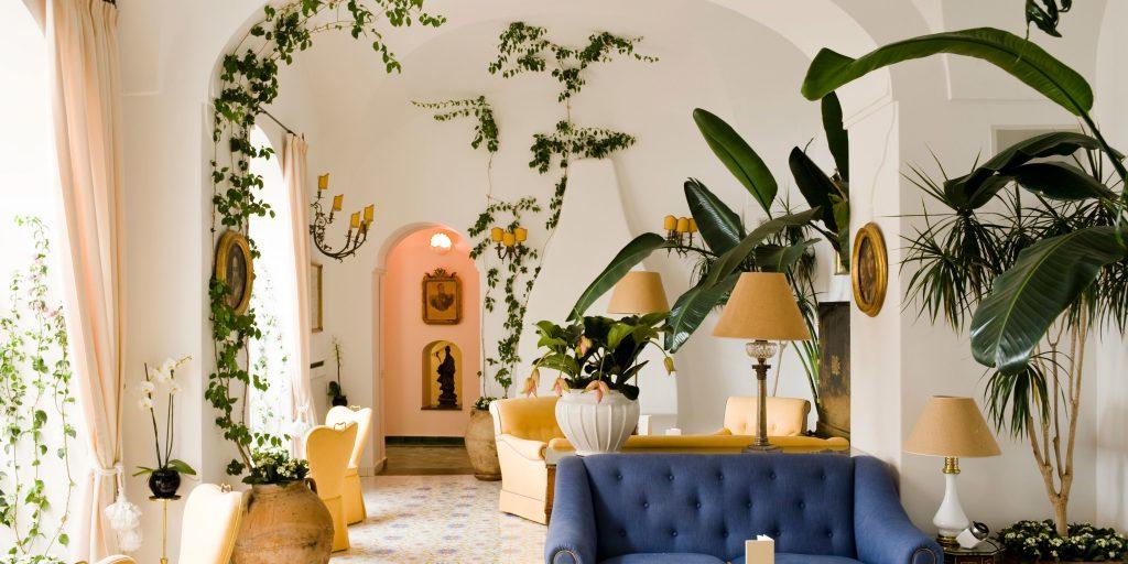 یک نشیمن بزرگ با سقف هلالی شد که مبل های زرد و سرمه ای در آن قرار داده شده است و با گل های بزرگ رونده ای تزیین شده است.