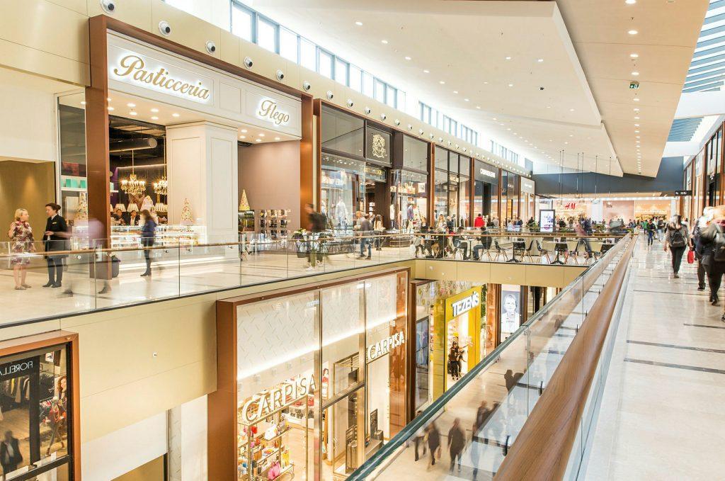 مرکز خرید دو طبقه  با نورپردازی زیاد که حفاظ های شیشه ای دارد و سقف سفید رنگ.