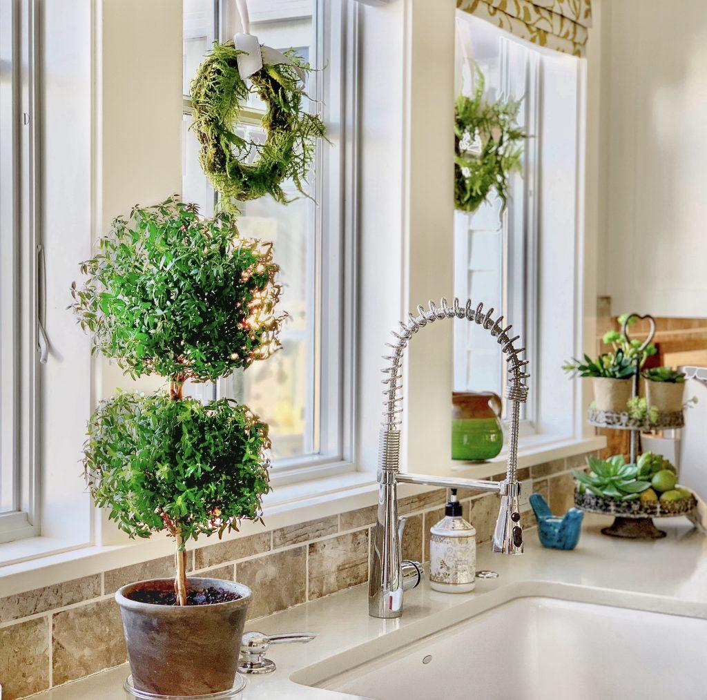 یک سینک مربعی شیر مدرن زیر دو پنجره که با گل های سبز تزیین شده است.
