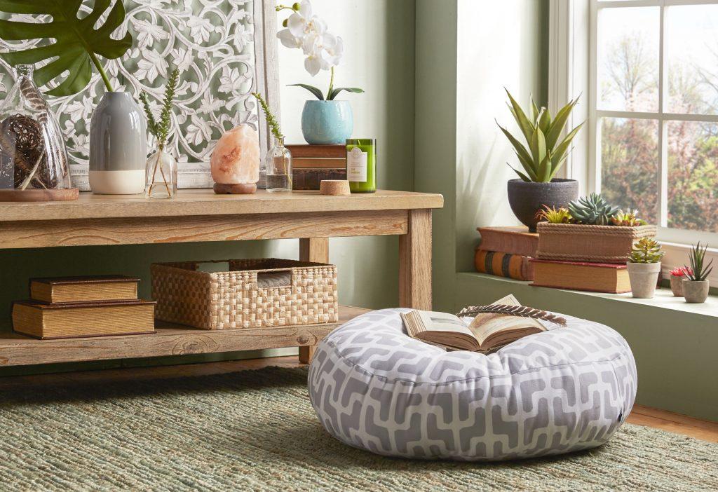تصویر یک پاف در کنار یک پنجره که کتابی روی آن واقع شده در اتاقی که با وسایل چوبی ارامش بخش تزیین شده است.