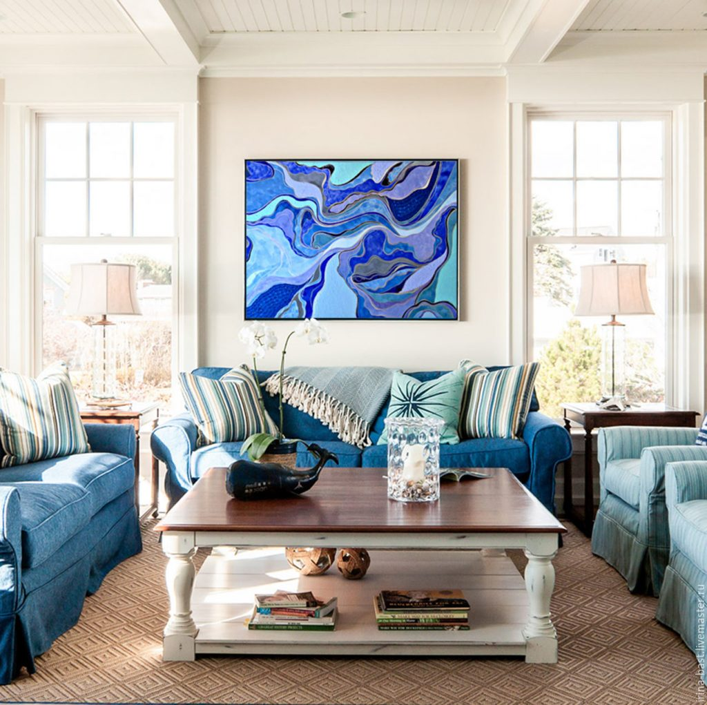 تاثیر نقاشی بر دکوراسیون فضای نشیمن با مبل های آبی رنگ که در مرکز دید تابلویی با رنگ آبی وجود دارد
