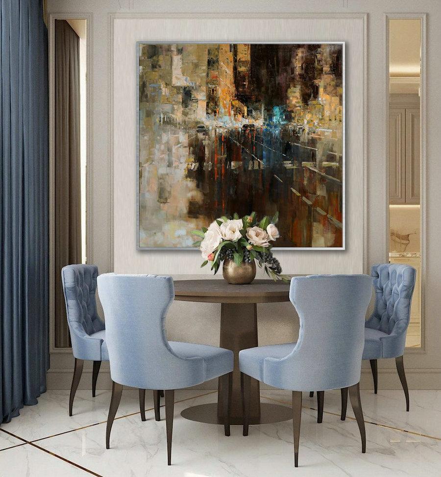 تصویری از یک میز ناهار خوری با صندای های آبی رنگ  که پشت آن تابلو  عمودی بزرگی قرار دارد