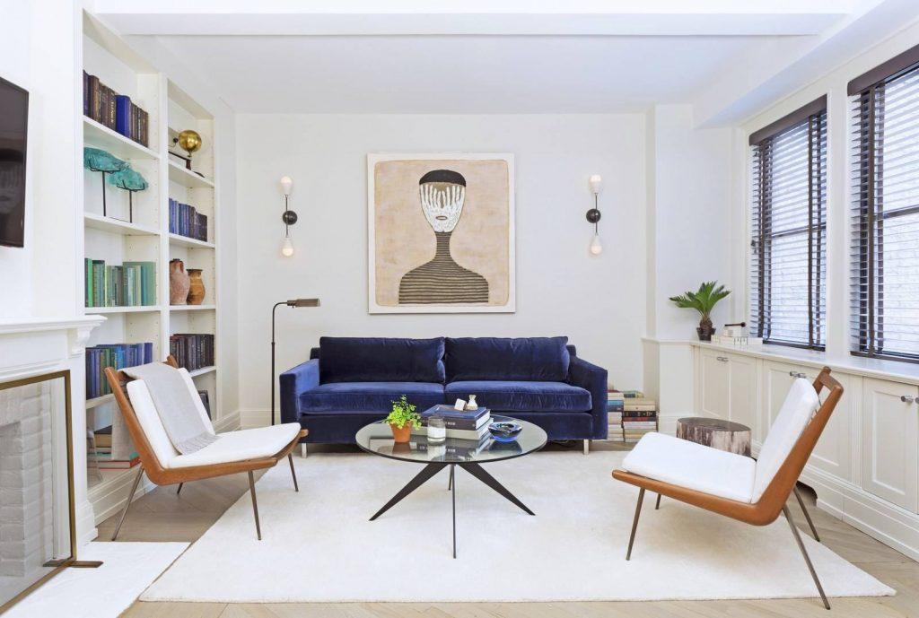 دکوراسیون منزل مدرن که کاناپه ای سورمه ای رنگ و دو صندلی تک نفره سفید رنگ دارد و میز گردی جلوی مبل ها و پشت کاناپه تابلویی از یک صورت وجود دارد