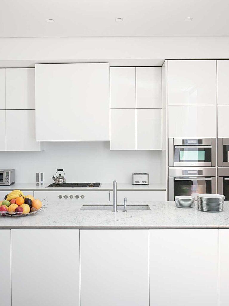 نمای آشپزخانه با سبک مدرن که یکپارچه  بودن و صاف براق بودن را باسفید بودن کابینت ها نشان میدهد