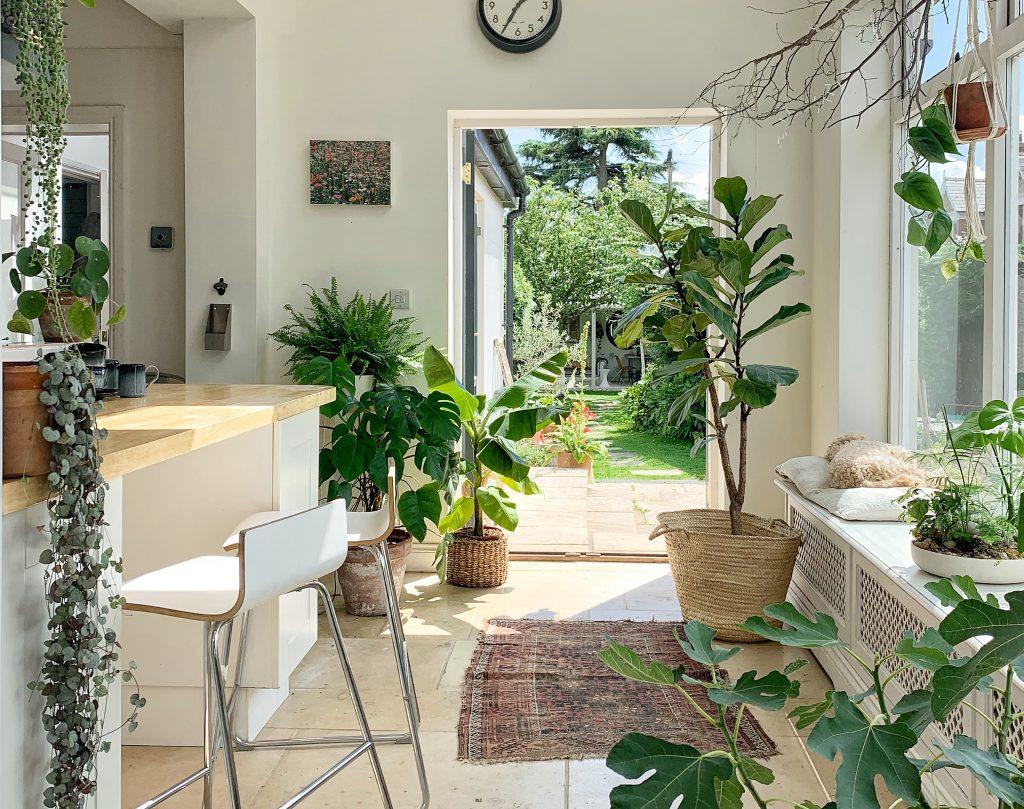 تصویر ورودی یک خانه که که با گل های بزرگی تزیین شده است و پنجره ی بزرگی در سمت راست و اوپن و دو عدد صندلی در کنار آن واقع شده است.