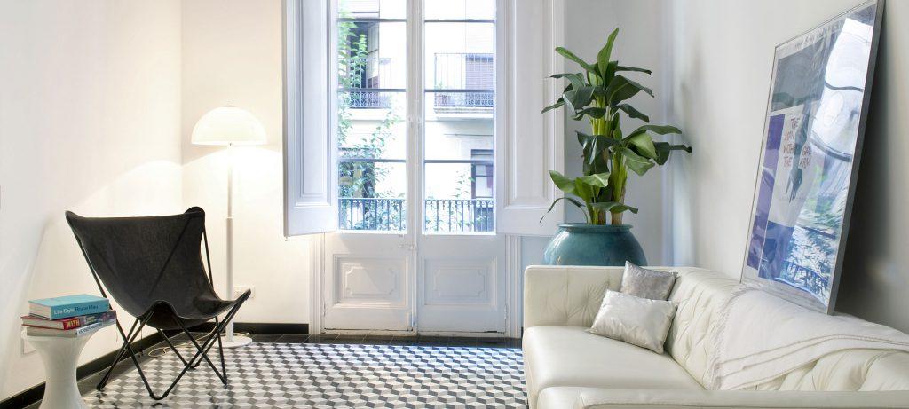 تصویر یک اتاق که یک مبل سفید راحتی در سمت راست و یک صندلی در سمت راست و یک گیاه آپارتمانی بزرگ در گوشه آن در کنار در بالکن واقع شده است.