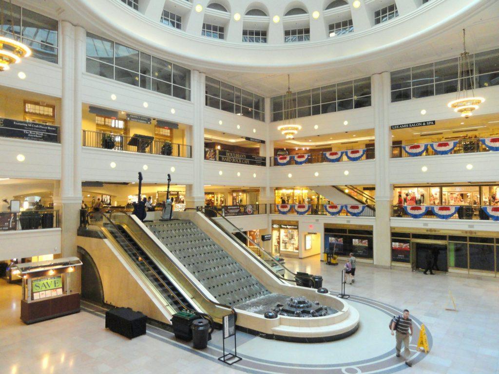 مرکز تجاری چند طبقه با سقف گنبدی شکل بلند که پله برقی در سمت چپ تصویر و آب نما در وسط آن واقع شده است.