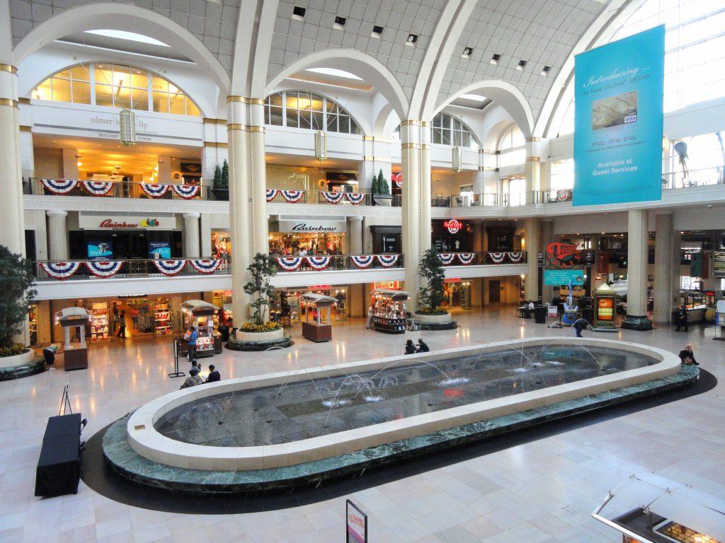 مرکز تجاری چند طبقه با سقف گنبدی شکل که یک آب نمای بیضی شکل بزرگ در وسط آن و ستون های جفتی در اطراف آن قرار دارد.