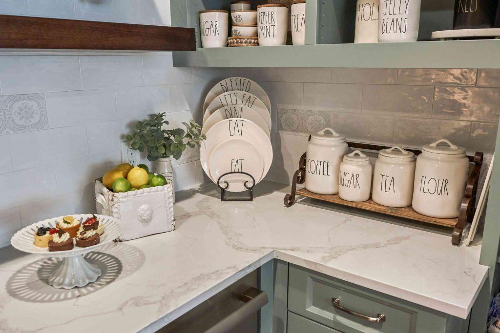 رویه کابینت کوارتز که با وسایل اَشپزخانه تزیین شده است مثل پایه بشقاب و ظروف خوراکی جات