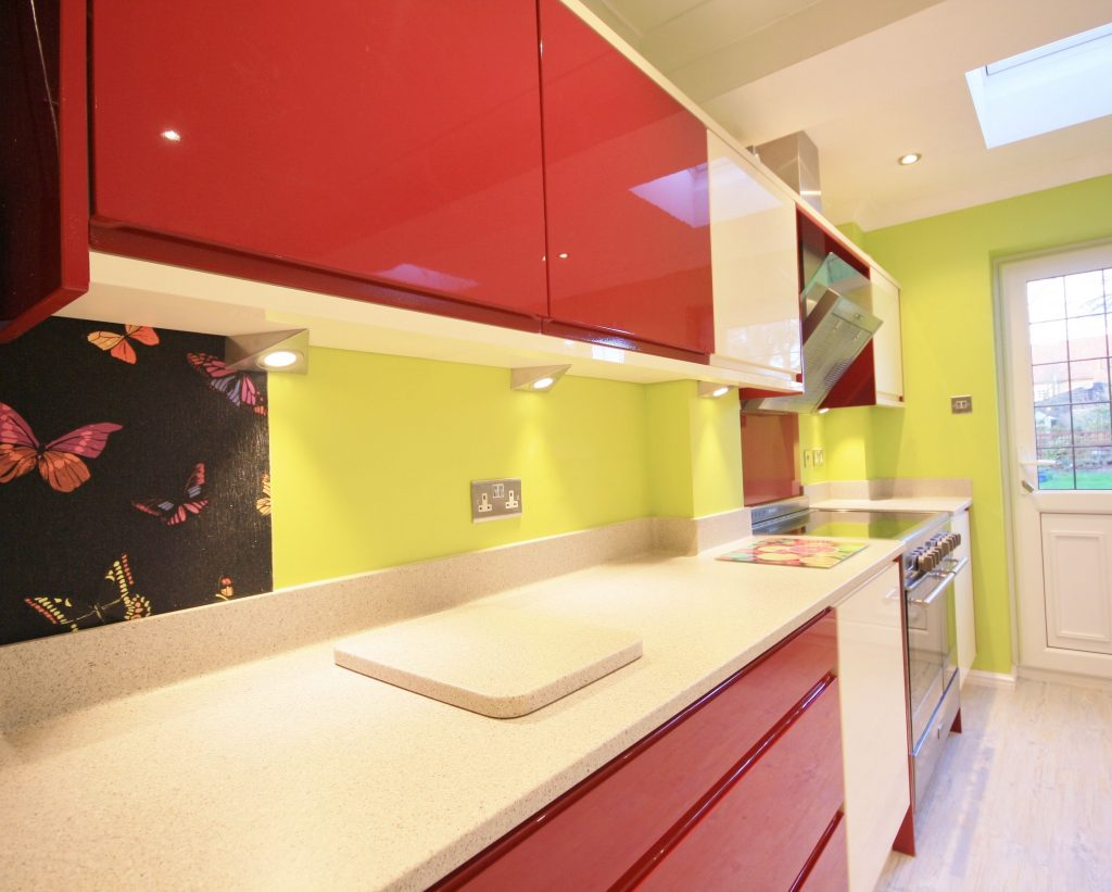 آشپزخانه ای با دیوارهای سبز رنگ و کابینت قرمز و صفحه کابینت کورین سفید