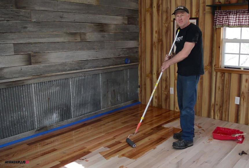 کارگر در لباس مشکی در حال رنگ کردن پارکت چوب طبیعی