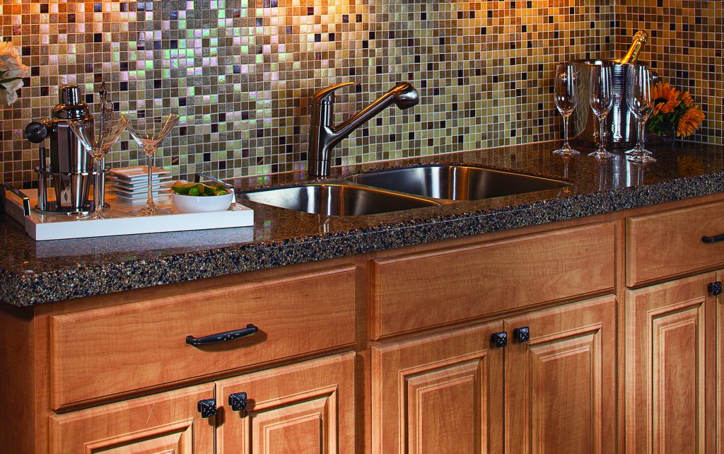 تصویر سینک دو لگنه و صفحه کابینت کورین قهوه ای با کابینت های به رنگ چوب که با جام هایی تزیین شده است