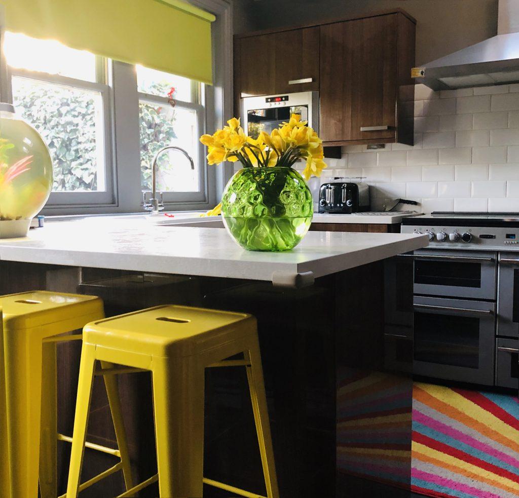 آشپزخانه ای با کابینت های قهوه ای رنگ و رویه ی سفید و صندلی های زردرنگ کنار اوپن . پنجره ای بزرگ که در بالای سینک قرار دارد.