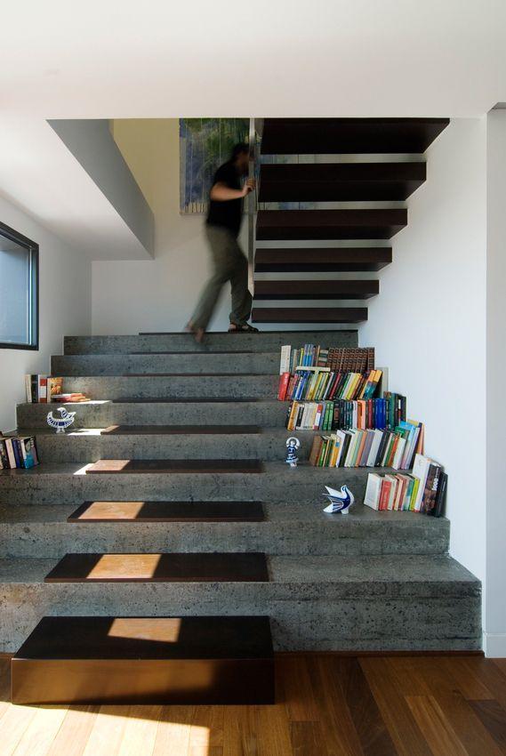 راه پله ای با کف پوش بتن،به رنگ طوسی که طول پله زیاد است به گونه ای که گوشه پله ها را کتا گذاشته اند به صورت کتابخانه استفاده کردند.