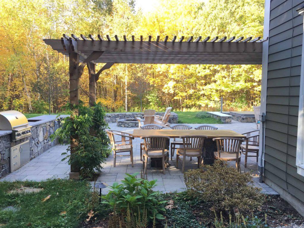پاسیویی دلنشین و کاربردی با دیواره های سنگی کوتاه و میزناهارخوری 8 نفره به رنگ چوب و فضای سبز و درخت کاری شده