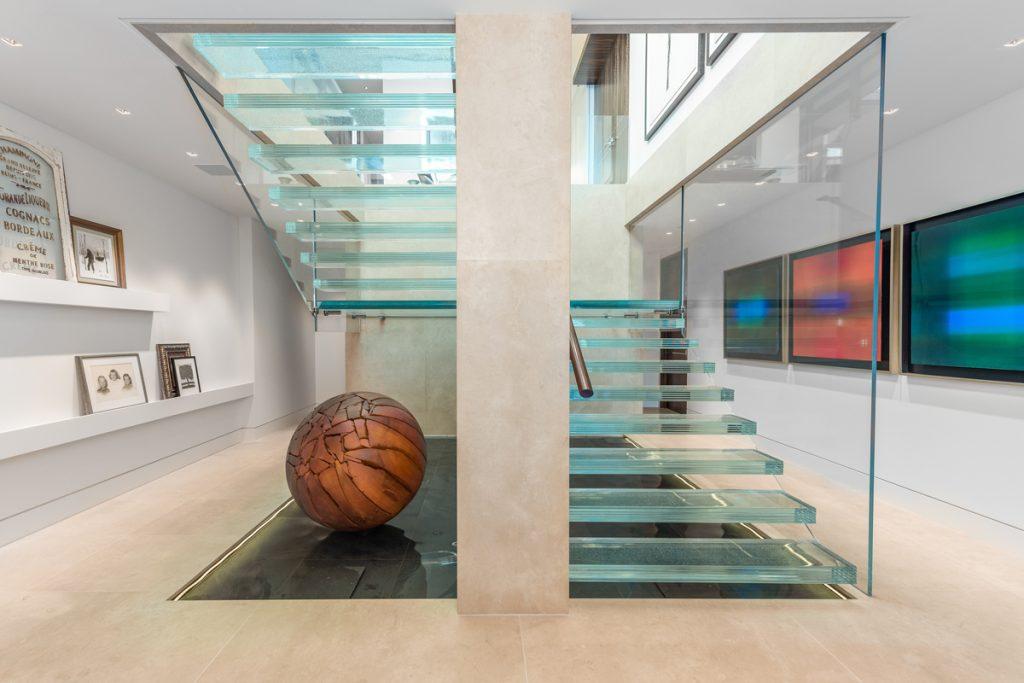 راه پله ای شیشه که دوتا پاگرد دارد، با حفاظ های شیشه ای