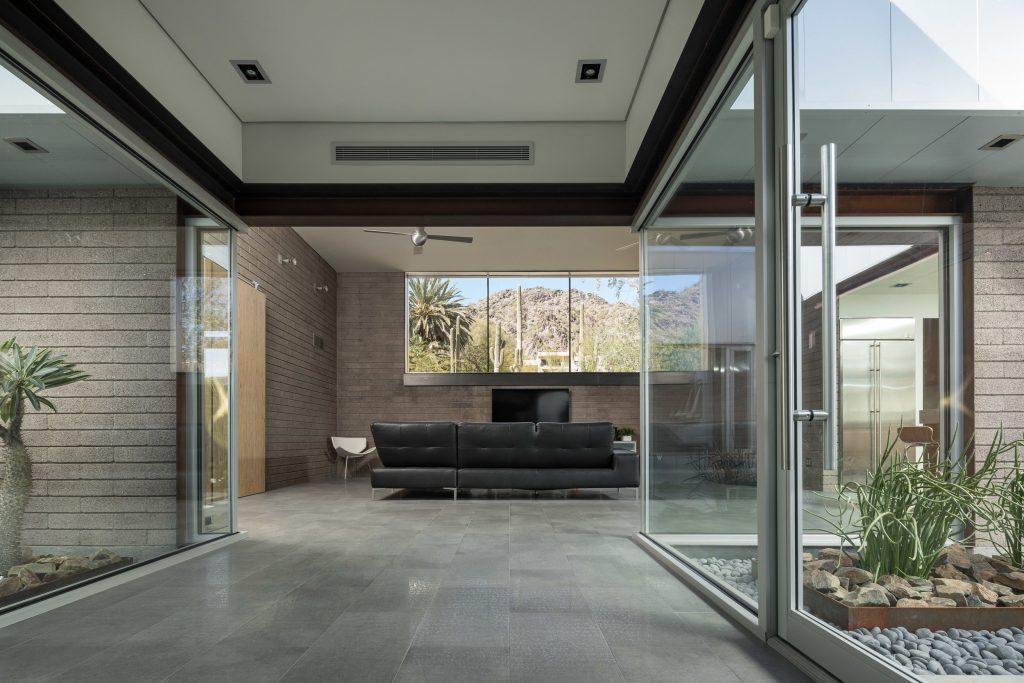 آتریوم های زیبا و دلنشین در داخل فضای ساختمان با دیوارهای شیشه ای و کف پوش سنگی که در دو سمت راهرو واقع شده است.