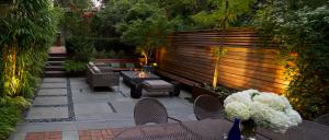 پاسیو یا دیوارهایی چوبی و کف سنگ و ریگ و تزیین شده با مبلمان و میز مدرن