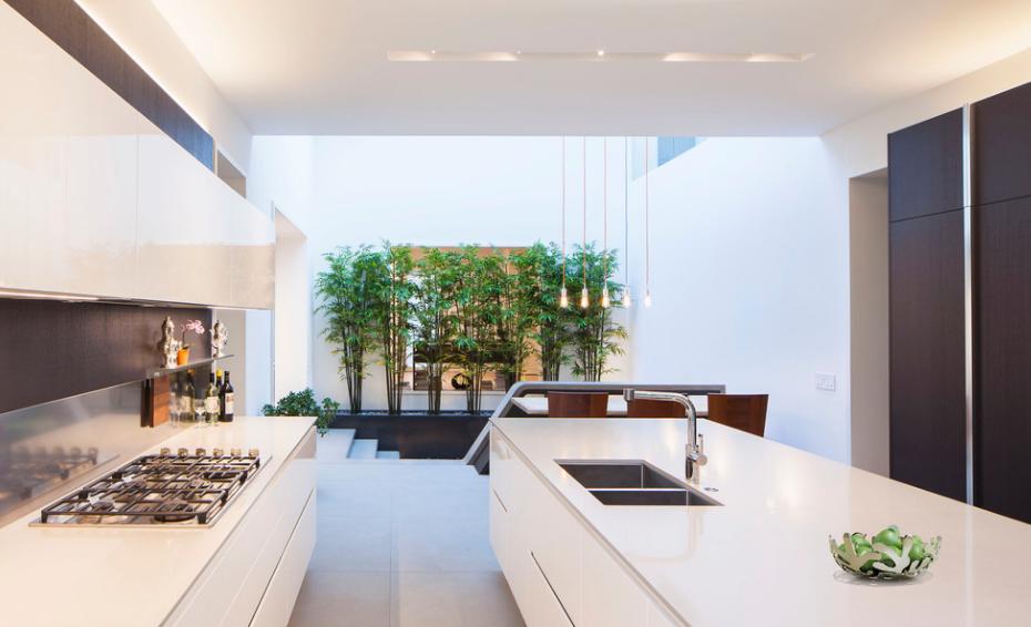 پاسیویی دلنشین در کنار راه پله و آشپزخانه ای با کابینت های سفید رنگ