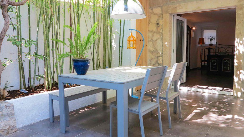 پاسیویی ساده و دلنشین که با یک میز ناهارخوری سفید رنگ و گیاهان بامبو تزیین شده است