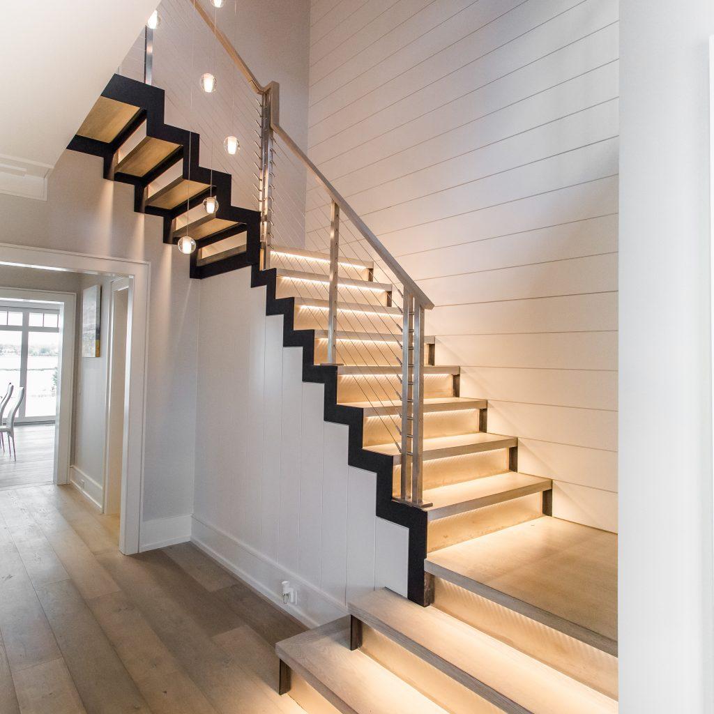 راه پله با کف پوش طرح چوب با رنگ روشن که به صورت خیلی حرفه ای روی پله ها نورپردازی شده است.